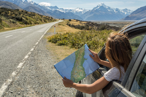 Map reading in car close to the New Zealand Alps